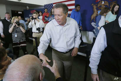 Republican presidential candidate, Ohio Gov. John Kasich shakes hands after speaking at a rally at the Monroe County Community College in Monroe, Michigan, March 7, 2016.