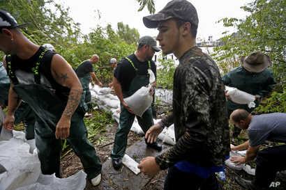 Volunteers put out sand bags before the arrival of Tropical Storm Cindy in Lafitte, La., June 21, 2017. Tropical Storm Cindy sent drenching rain bands over the north Gulf Coast Wednesday, swamping low-lying coastal roads and pushing a waterspout asho...