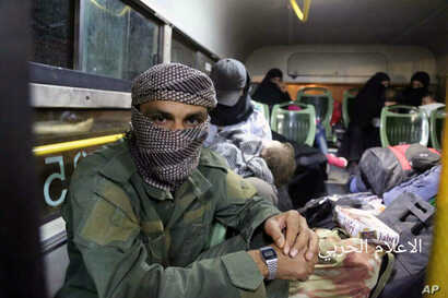 FILE -  Aug. 3, 2017 photo released by the government-controlled Syrian Central Military Media, shows al-Qaida-linked militants seated in a bus with their families, after being evacuated from the town of Arsal, near the Syrian border, in northeast Le...