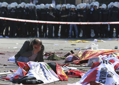A man cries over the body of a victim, at the site of an explosion in Ankara, Oct. 10, 2015.