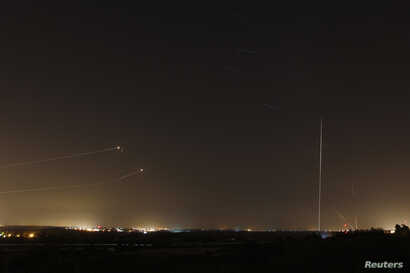 Rockets launched from the Gaza Strip towards Israel is seen (at right) as a rocket by the Iron Dome anti-missile system (at left) is fired to intercept them, before a five-day ceasefire was due to expire, August 19, 2014. A ceasefire in the Gaza Stri...