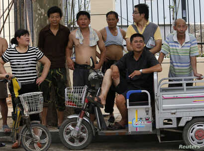 Bystanders look at the Jinan Municipality People's Intermediate Courthouse building, where the trial for disgraced Chinese politician Bo Xilai is likely to be held in Jinan, Shandong province, July 25, 2013. China has charged disgraced former senior ...