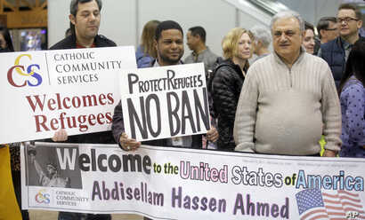 Refugee supporters look on after Abdisellam Hassen Ahmed, a Somali refugee who had been stuck in limbo after President Donald Trump temporarily banned refugee entries, arrives at Salt Lake International Airport in Salt Lake City, Utah., Feb. 10, 2017...