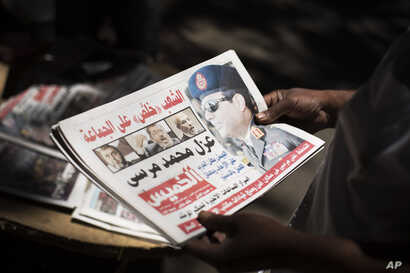Egyptian man holds a newspaper the news near Mesaha Square, in Cairo , Thursday, July 4, 2013. The chief justice of Egypt's Supreme Constitutional Court was sworn in Thursday as the nation's interim president, taking over hours after the military ous...