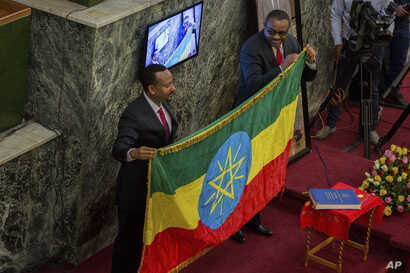The outgoing prime minister, Haileamariam Dessalegn, right, who resigned from his post symbolically hands over the Ethiopian flag to Abiye Ahmed, left,  April 2, 2018.