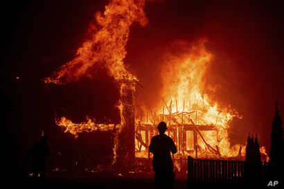 A home burns as the Camp Fire rages through Paradise, Calif., Nov. 8, 2018.