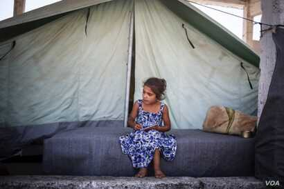 Silva, 7, writes in a notebook in front of her family's tent at the Alexandria refugee camp in northern Greece. (Photo: courtesy: Tara Todras-Whitehill/IRC)
