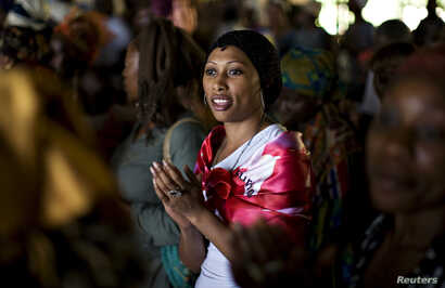 FILE - A woman sings during a prayer session at the Saint Francis Xavier parish, part of the fraternity Ephphata charismatic awakening branch of the Catholic church, ahead of the arrival on Tuesday of Pope Benedict XVI in Yaounde March 17, 2009.