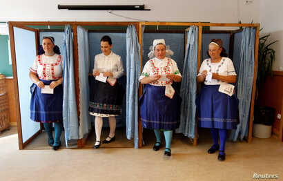 Hungarian women wearing traditional costume leave a voting booth at a polling station during a referendum on EU migrant quotas in Veresegyhaz, Oct. 2, 2016.