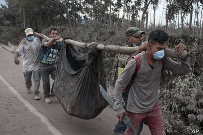 """Residents carry a body recovered near the """"Volcano of Fire,"""" in Escuintla, Guatemala,  June 4, 2018."""