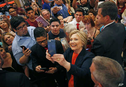 Democratic presidential candidate Hillary Clinton takes a selfie with supporters at a rally, in El Centro, Calif., June 2, 2016.