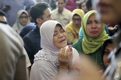A relative of passengers prays as she and others wait for news on a Lion Air plane that crashed off Java Island at Depati Amir Airport in Pangkal Pinang, Indonesia Monday, Oct. 29, 2018.