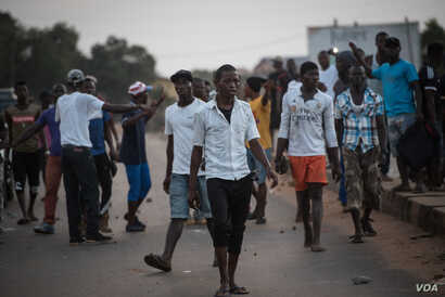 Supporters of the opposition Sierra Leone People's Party walk after clashing with police outside party headquarters in Freetown's Goderich neighborhood, March 7, 2018. (J. Patinkin/VOA)