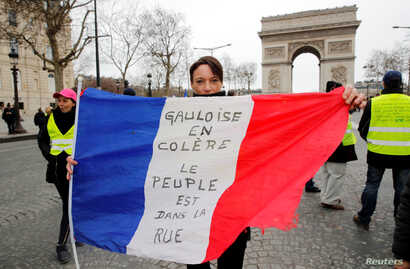 """A protester holds the French flag on the Champs-Elysees near the Arc de Triomphe during a demonstration by the """"yellow vest"""" movement in Paris, March 9, 2019. The writing on the flag reads: """"Gauls are angry. The people are on the street."""""""