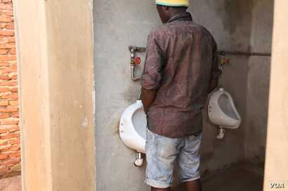 Peeing is a source of wealth to most residents of Area 25A in the capital Lilongwe - this man is peeing for a purpose inside the urine harvesting plant. (L. Masina/VOA)