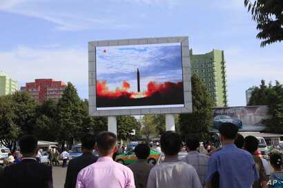 FILE - People watch a launching of a Hwasong-12 strategic ballistic rocket aired on a public TV screen at the Pyongyang Train Station in Pyongyang, North Korea, Sept. 16, 2017.