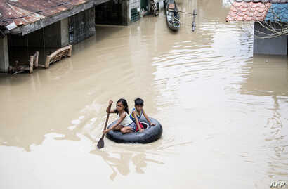 Children use a tyre's interior to cross a flooded street in the aftermath of Super Typhoon Mangkhut at Salonga Compound in Calumpit, Bulacan on September 16, 2018.