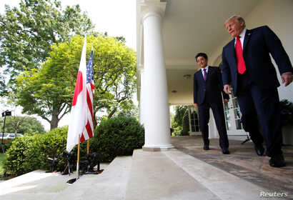Japan's Prime Minister Shinzo Abe and U.S. President Donald Trump arrive for a joint news conference in the Rose Garden of the White House in Washington, June 7, 2018.