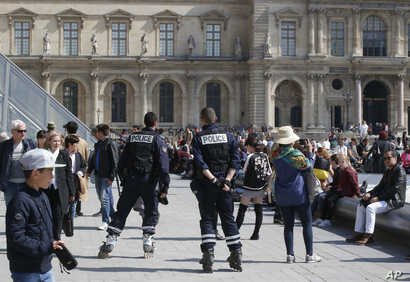 Police officers patrol outside the Louvre museum, April 21, 2017 in Paris.