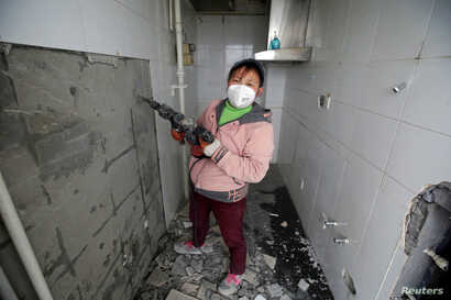 Deng Qiyan, 47, a mother of three and a decoration worker at contraction sites, poses for a photograph at an apartment building under construction in Beijing, China, Feb. 22, 2017.