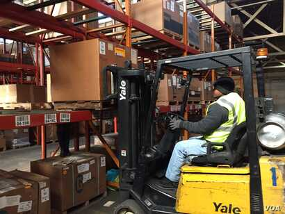 Ex-offender Wade Tate drives a forklift for DSI Warehouse in greater Memphis, Tenn. His boss says customers ask to meet Tate in person to offer thanks for his computer assistance with their orders. (C. Presutti / VOA)