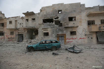 A damaged vehicle is seen near buildings in the northern Syrian town of al-Bab, Syria, March 1, 2017.