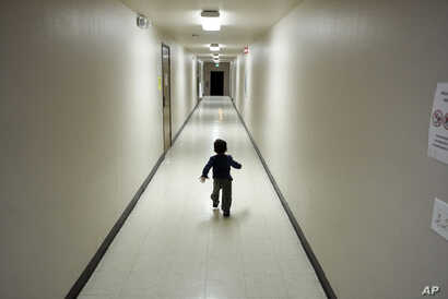 FILE - An asylum-seeking boy from Central America runs down a hallway after arriving from an immigration detention center to a shelter in San Diego, Calif., Dec. 11, 2018.