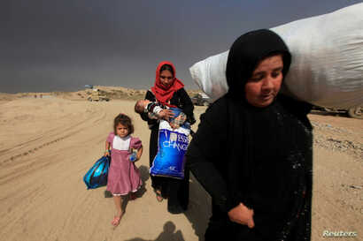 Displaced people who are fleeing from clashes arrive in Qayyarah, during an operation to attack Islamic State militants in Mosul, Iraq on Oct. 19, 2016.