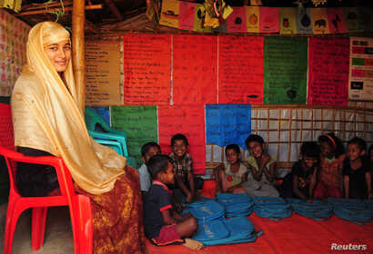 Nur Jahan, sister of Formin Akter, a Rohingya refugee girl, sits with her students inside her shelter, where she teaches, at the Kutupalong refugee camp in Cox's Bazar, Bangaldesh Dec. 4, 2018.