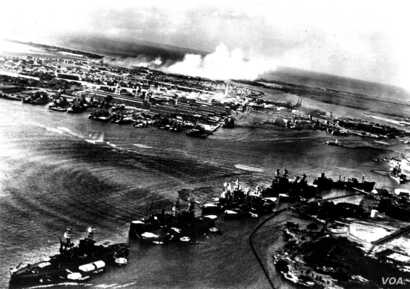This image was captured by a Japanese naval aviator in the opening moments of the attack on Pearl Harbor. Torpedo tracks can be seen headed towards Battleship Row. Smoke rises in the distance from the burning aircraft and hangars at Hickam Field.