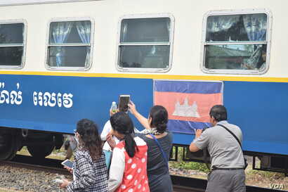 Excited tourists take photographs of a train during a break at Kampot station. (D. de Carteret/VOA)