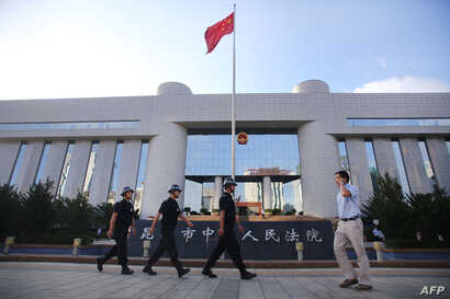 Police patrol at the gate of Kunming's Intermediate Court in Kunming, southwest China's Yunnan province, Sept. 12, 2014.