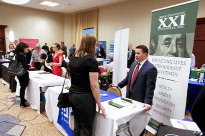Corporate representatives speak with job seekers at a job fair in Pittsburgh, Pennsylvania, March 30, 2016.
