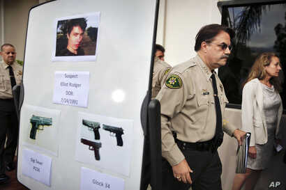 FILE- This May 24, 2014, photo shows Santa Barbara County Sheriff Bill Brown, right, after a news conference as he walks past a board showing photos of gunman Elliot Rodger and the weapons he used in a mass shooting the day before in Isla Vista, Cali...