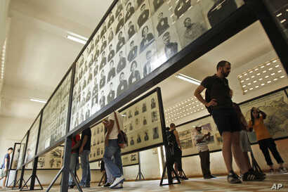 FILE - Tourists view portraits of victims executed by the Khmer Rouge regime at the Tuol Sleng Genocide Museum, formerly a notorious Khmer Rouge prison, in Phnom Penh, Cambodia, April 9, 2015.