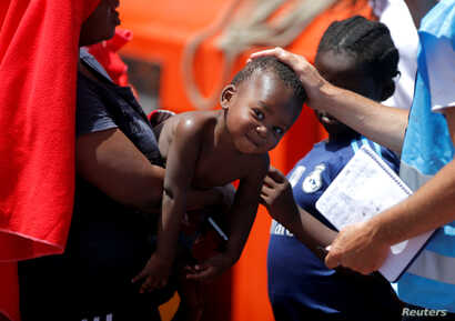A member of Frontex touches a migrant child, intercepted aboard a dinghy off the coast in the Strait of Gibraltar, after arriving on a rescue boat at the port of Algeciras, southern Spain, July 21, 2018.