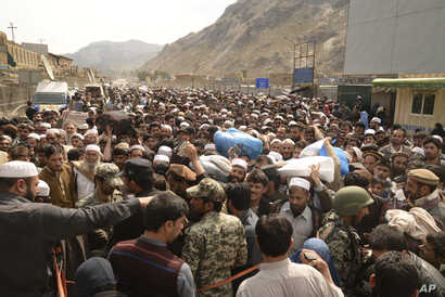 FILE - Afghan nationals prepare to cross the Torkham border post in Pakistan en route to Afghanistan, March 7, 2017.