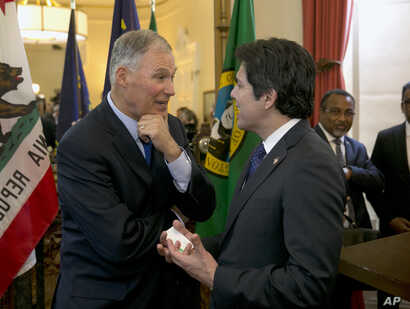 Washington Gov. Jay Inslee, left, talks with California Senate President Pro Tem Kevin de Leon after a news conference, held by California Gov. Jerry Brown, June 13, 2017, in Sacramento, California.