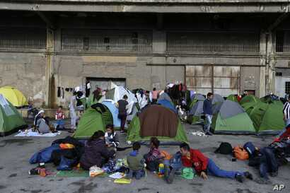 Refugees and migrants sit outside their tents at the Athens' port of Piraeus, March 10, 2016.