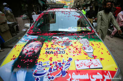 FILE - A resident walks past a parked car decorated with a poster of Mohammad Yaqoob Sheikh, candidate of the Milli Muslim League political party, during an election campaign for the National Assembly NA-120 constituency in Lahore, Pakistan, Sept. 9,...