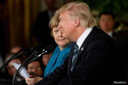 Germany's Chancellor Angela Merkel, left, gives U.S. President Donald Trump a look after he suggested they might have something in common, as he answered a question about his accusation that he had been wiretapped by former President Barack Obama, du...