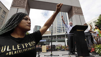 Mara Jacqueline Willaford of the Seattle chapter of Black Lives Matter, left, holds her fist overhead as Democratic presidential candidate Sen. Bernie Sanders, I-Vt., waves to greet the crowd before speaking at a rally in downtown Seattle, Washington...