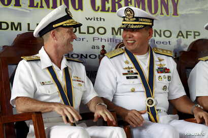 Philippine Navy Rear Admiral Leopoldo Alano (R) shares a light moment with U.S. Navy Rear Admiral William Merz during the opening ceremony of the  Cooperation Afloat Readiness and Training (CARAT) 2015 at navy headquarters in Puerto Princesa city, Pa...