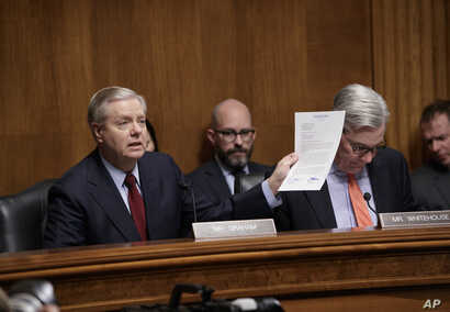 Sen. Lindsey Graham, R-S.C., chairman of the Senate Judiciary subcommittee on Crime and Terrorism, joined by Sen. Sheldon Whitehouse, D-R.I., the ranking Democrat, displays a letter to FBI Director James Comey saying Congress needs to get to the bott...