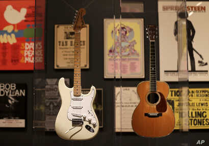 "Guitars used by Jimi Hendrix, left, and Eric Clapton are displayed with concert posters at the exhibit ""Play It Loud: Instruments of Rock & Roll,"" at the Metropolitan Museum of Art in New York, April 1, 2019."