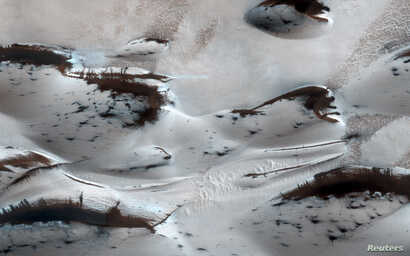 FILE - Water? Not anymore. Mars' northernmost sand dunes are seen as they begin to emerge from their winter cover of seasonal carbon dioxide (dry) ice in this image acquired by the HiRISE camera aboard NASA's Mars Reconnaissance Orbiter, Jan. 16, 2...