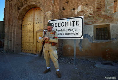 A man dressed as a Republican soldier waits for tourists in front of the entrance to the old village of Belchite.