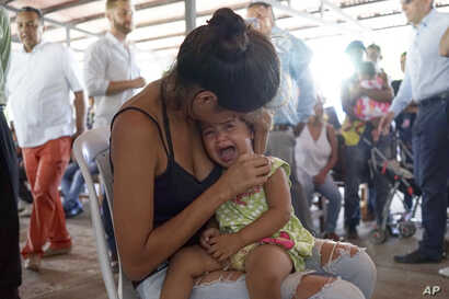 A Venezuelan woman holds a girl at a health post for migrants in Cucuta, along Colombia's border with Venezuela, July 16, 2018.