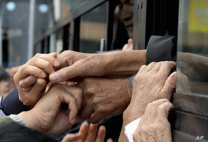 South Koreans and their North Korean relatives on a bus grip their hands each other to bid farewell after the Separated Family Reunion Meeting at Diamond Mountain resort in North Korea, Oct. 22, 2015.