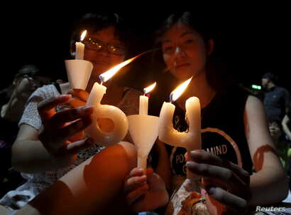 "Pro-democracy supporters hold candles in the shape of ""64"", which symbolizes ""June 4th"", during an annual candlelight vigil at Victoria Park in Hong Kong, China, June 4, 2015 to mark Beijing's Tiananmen Square crackdown in 1989."